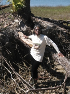 Queen Quet, Chieftess of the Gullah/Geechee Nation (www.QueenQuet.com) and a Founding Member and Secretary of the Gullah/Geechee Fishing Association stands amidst the exposed roots of a tree on Hunting Island just a few feet from the marsh to show the effects of climate change on the Gullah/Geechee Nation's coast.