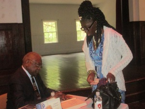 Congressman James E. Clyburn signs a book for Queen Quet